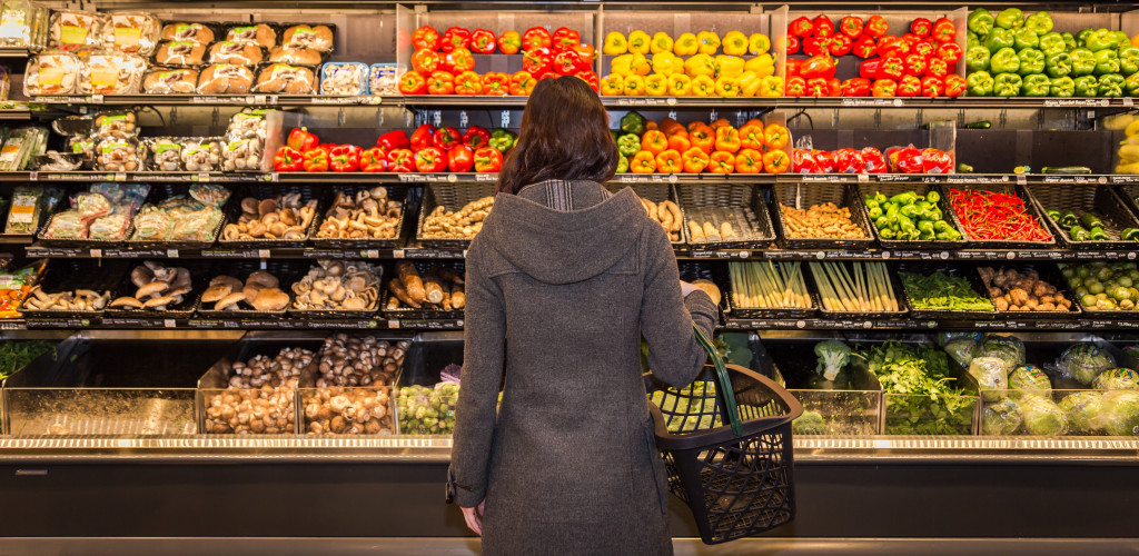 A girl standing in front fruits and vegetable